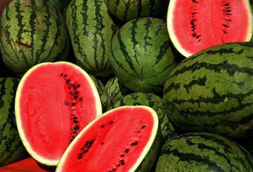 Image of lots of watermelon with their red flesh and seeds inside